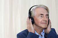 Senior man wearing headphones head and shoulders in studio