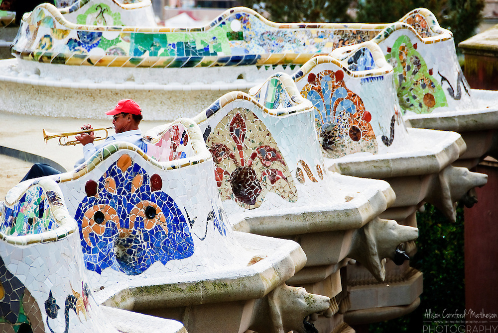 A trumpet player plays a song while relaxing on the Wavy Bench at Park Guell. Antoni Gaudi's Park Guell is a UNESCO World Heritage Site.
