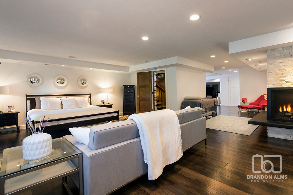 A modern basement living space with fireplace. Photo by Brandon Alms Photography