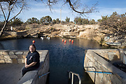 Dive shop operator Stella Salazar sits next the Blue Hole in Santa Rosa New Mexico. - Steven St. John for New Mexico Magazine