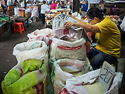 29 JUNE 2015 - BANGKOK, THAILAND: A woman selling rice reads the newspaper while she waits for customers in the Bang Chak Market in Bangkok. The Bang Chak Market serves the community around Sois 91-97 on Sukhumvit Road in the Bangkok suburbs. About half of the market has been torn down, vendors in the remaining part of the market said they expect to be evicted by the end of the year. The old market, and many of the small working class shophouses and apartments near the market are being being torn down. People who live in the area said condominiums are being built on the land.     PHOTO BY JACK KURTZ