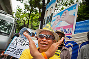 "22 JUNE 2011 - BANGKOK, THAILAND: A Thai Yellow Shirt calls for a no vote in front of campaign posters from other parties during a pre-election rally in Bangkok on Wednesday, June 22. The PAD (People's Alliance for Democracy) or Yellow Shirts, as they are popularly called, has called for a ""No"" vote in Thailand's national election, scheduled for July 3. PAD leadership hopes the no vote will negate the vote of Yingluck Shinawatra, leader of the Pheua Thai party. Yingluck is the youngest sister of exiled former Prime Minister Thaksin Shinawatra, deposed by a military coup in 2006. Yingluck is currently leading in opinion polls, running well ahead of incumbent Prime Minister Abhisit Vejjajiva, head of the Democrat party, which in one form or another has ruled Thailand for most of the last 60 years.     Photo by Jack Kurtz"