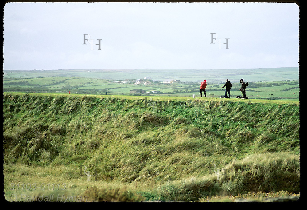 Golfers tee off at edge of ravine on the difficult, undulating links of Lahinch Golf Course, County Clare, Ireland.