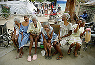 Rene Rithanne at center sits on a bench waiting for her bath along with other elderly ladies outside  the Municipal Nursing Home in Port-A-Prince near Delmas 2 on February 27, 2010. The nursing home was destroyed during the earthquake and now the general public has encroached on the nursing home site.