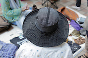 person with a large brim hat at a secondhand outdoors clothing flee market