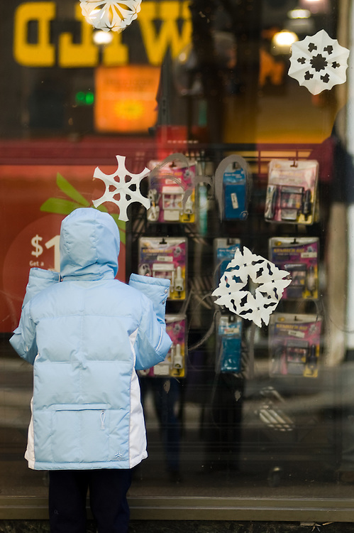 A child looks through the window at a downtown Denver store before Christmas.