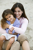 Mother embracing daughter on beach
