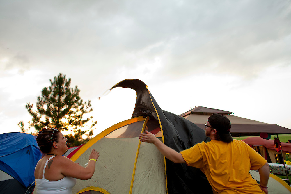 Jen Wilson and Mark Keitel help set up a rain fly at Camp Euforia, north of Lone Tree, on Thursday, July 16, 2015. The annual festival has become a place to reunite with old friends and discover new music, and regularly draws roughly a thousand campers.