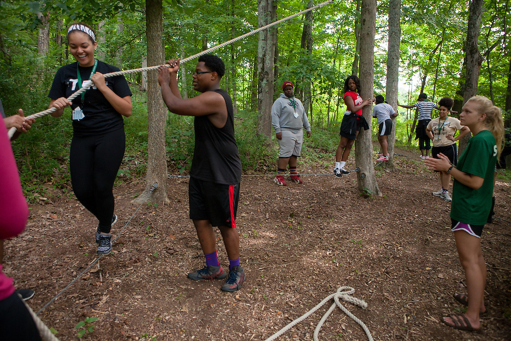 Participants in Ohio University's Junior Executive Business Program help each other walk cables between trees during the Ropes Challenge Course on July 13, 2014. Photo by Lauren Pond