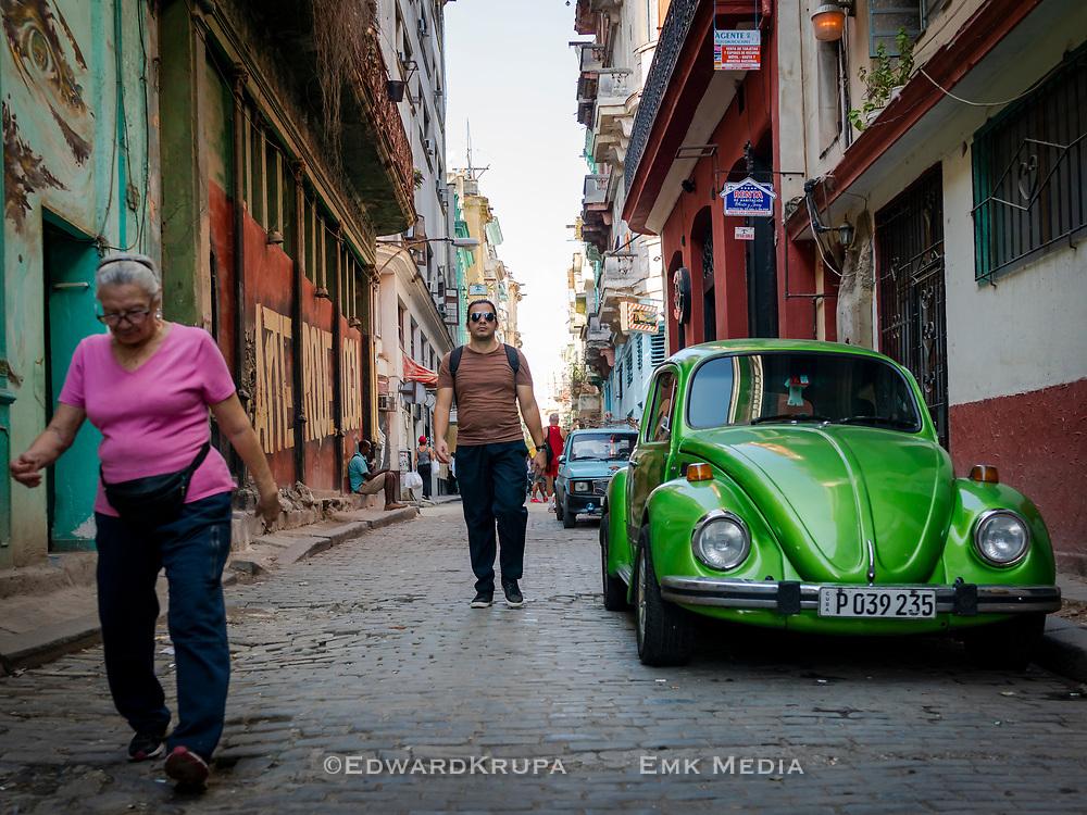 A man, wearing aviator sunglasses, walking on a street by a parked green Volkswagen Bug in Old Havana.