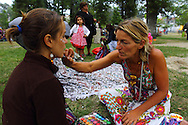 Face painting in the village green park during the exhibitions for thanking for the hospitality at the small village of Salto, Montalegre. European Rainbow Gathering of 2011 in Portugal
