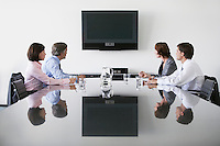 Four business colleagues watching flat screen television in conference room