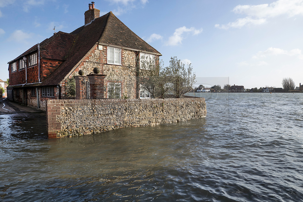 © Licensed to London News Pictures. 03/01/2018. Bosham, UK. A house is surrounded by tidal flood water at Bosham as storm Eleanor hits the south. Winds of up to 80 mph are being forecast today in parts of the UK. Photo credit: Peter Macdiarmid/LNP