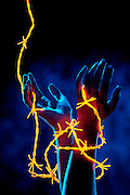 Pleading hands entangled in glowing barbed wire .Black light