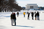 Tourists talk photographs and walk on the frozen reflecting pool in front of the Lincoln Memorial in Washington D.C. following the bizzard of 2010.
