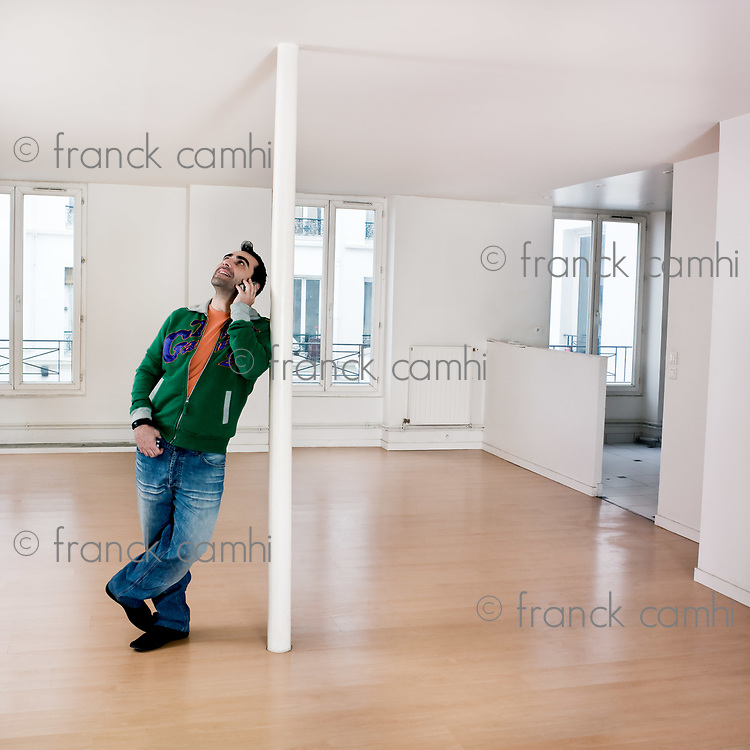 man alone inside an empty loft appartement calling by phone