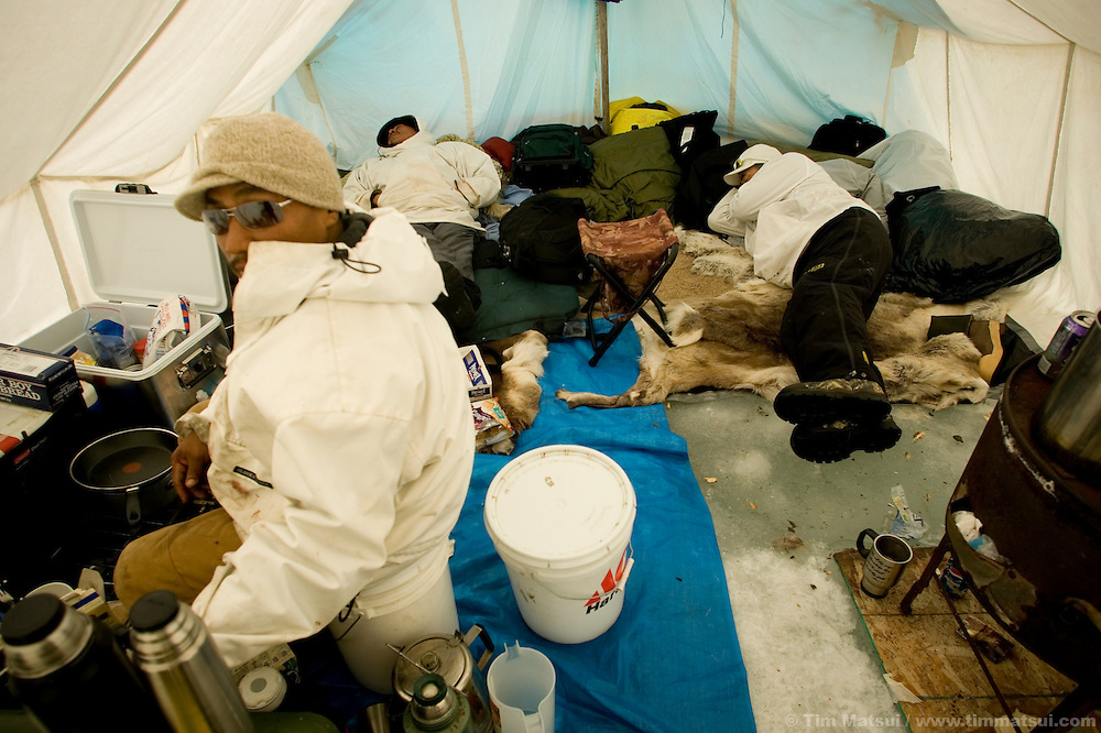 May 3, 2008 -- Kivalina, AK, U.S.A..Terry Baldwin cooks rice while two crew members sleep at Austin Swan's whaling camp, two miles out on the melting pack ice and 12 miles from the native village of Kivalina, Alaska. Kivalina is suing 20 oil companies for property damage related to global warming; the ocean pack ice forms later and melts earlier, leaving the town vulnerable to erosive winter storms and endangering their traditional subsistence lifestyle. (Photo by Tim Matsui)