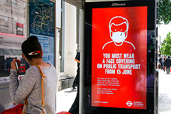 © Licensed to London News Pictures. 13/06/2020. London, UK. A woman looks at 'YOU MUST WEAR A FACE COVERING ON PUBLIC TRANSPORT FROM 15 JUNE', the government's new public information campaign displayed at a bus stop in north London. <br /> Face covering will be compulsory on buses, trains, trams and planes from Monday 15 June. Secretary of State for Transport, Grant Shapps has said that, people who do not wear face covering on public transport from Monday could be fined up to £100. Photo credit: Dinendra Haria/LNP