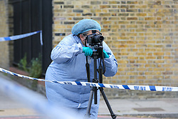 © Licensed to London News Pictures. 12/05/2019. London, UK. A forensics officer on Tollington Road at the junction of Annette Road, Islington in north London as Met police launch an investigation into the death of a man who was found in a wheelie bin behind a Waitrose store shortly before 4pm on Saturday 11 May 2019.. Photo credit: Dinendra Haria/LNP