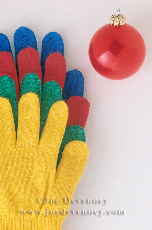Colorful gloves in the snow with a red Christmas ornament.
