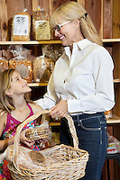 Happy senior woman with granddaughter looking at each other while holding bread basket in market
