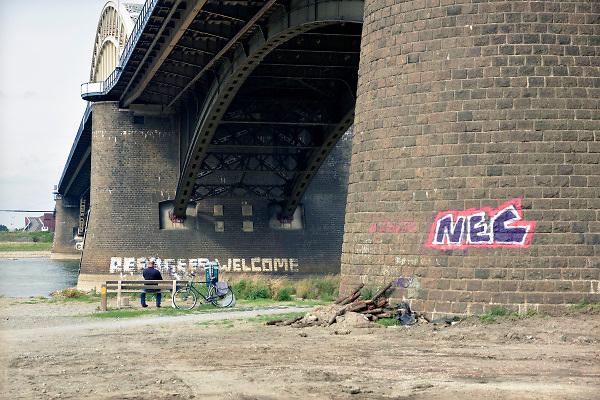 Nederland, Nijmegen, 7-9-2018 Rechtse activisten hebben de tekst Refugees Welcome die op een peiler van de Waalbrug geschreven staat met witte verf verminkt. Zij vinden dat de tekst niet strookt met hun standpunt over migratie. Er is wat ophef over in linkse kringen.Foto: Flip Franssen