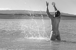 not male nude splashing water in a lake