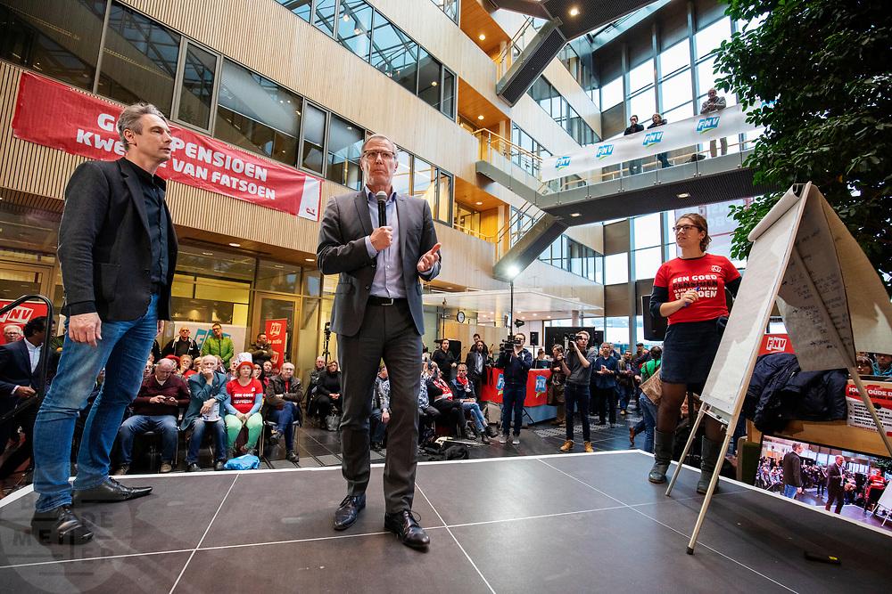 Voorzitter Han Busker (midden) en vice-voorzitter Tuur Elzinga spreken de menigte toe. In Utrecht zijn zo'n duizend FNV-leden bij het vakbondshuis gekomen om als actieberaad te praten over de eerder besproken hoofdlijnen van het actieplan vast te stellen. De vakbond komt in actie na het mislukken van het pensioenakkoord waarvoor de vakbond de schuld heeft gekregen.<br /> <br /> Chairman Han Busker and vice- chairman Tuur Elzinga talk to the audience. In Utrecht around thousand members of the trade union FNV gather to discuss the actions the trade union has to take after the collapse of an agreement on the pensions with the government.