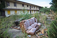 July 17, Eastern New Orleans, Discarded couch in front of abandoned housing projects destroyed by Hurricane Katrina in 2005.