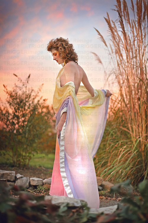A blonde woman walking away in a backless rainbow dress into the colorful sunset.