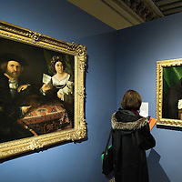 "VENICE, ITALY - NOVEMBER 23:  A woman stands between ""Ritratto di due Coniugi"" and ""Ritratto di un Domenicano"" at the press preview of Tribute to Lorenzo Lotto - The Hermitage Paintings at Accademia Gallery on November 23, 2011 in Venice, Italy. The exhibition which includes two very rare & never seen before paintings opens from the 24th November 2011 to 26th February 2012 in Italy."