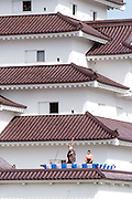 An archer fires an arrow from the roof of Tsuruga-jo castle to mark the start of the 2015 Aizu Festival in Aizuwakamatsu City, Fukushima Prefecture, Japan.  Photographer: Rob Gilhooly