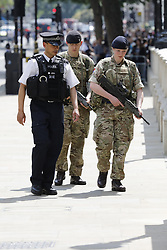 © Licensed to London News Pictures. 24/05/2017. London, UK. Police and army patrol in Whitehall, Westmisnter. The terrorism threat level has been raised to critical and Operation Temperer has been deployed. 5,000 troops are taking over patrol duties under police command. Photo credit: Peter Macdiarmid/LNP