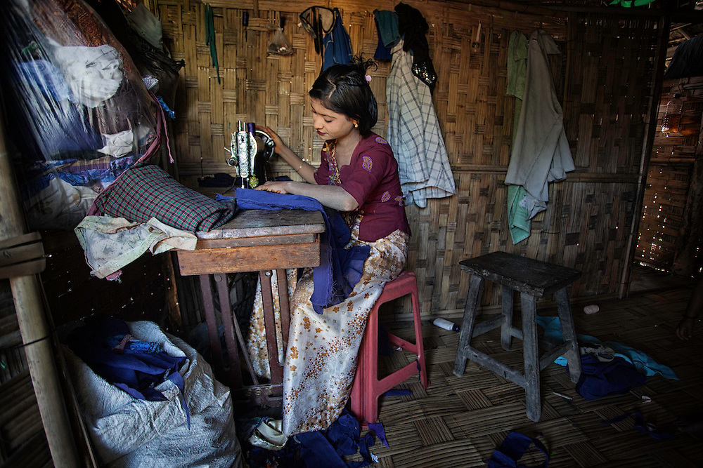 Sobeerakatton Kassim, 15, works ar a sewing maching at friends bamboo hut at the Basara IDP camp on the outskirts of Sittway, Myanmar, Dec. 17, 2013. Recent tension in Myanmar have forced thousands of ethnic Rohingya Muslims into makeshift camps.