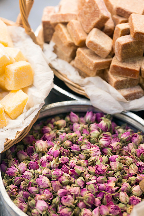 FEZ, MOROCCO - 1st DECEMBER 2016 - Soaps for the hammam and dried rose flowers from Kelaat M'Gouna for sale at a market stall in the old Fez Medina, Morocco.