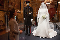 © Licensed to London News Pictures. 25/10/2018. Windsor, UK. Curator Caroline de Guitar views The Duchess of Sussex's wedding dress which was created by the British designer Clare Waight Keller Artistic Director at the historic French fashion house Givenchy. The Duke of Sussex uniform is from the Household Cavalry(the Blues and Royals. The outfits are on display at The Royal Collection at Windsor Castle. PLEASE NOTE, THIS PHOTO IS EMBARGOED FOR PUBLICATION UNTIL 00:01 FRIDAY 26 OCTOBER 2018. Photo credit: Ray Tang/LNP