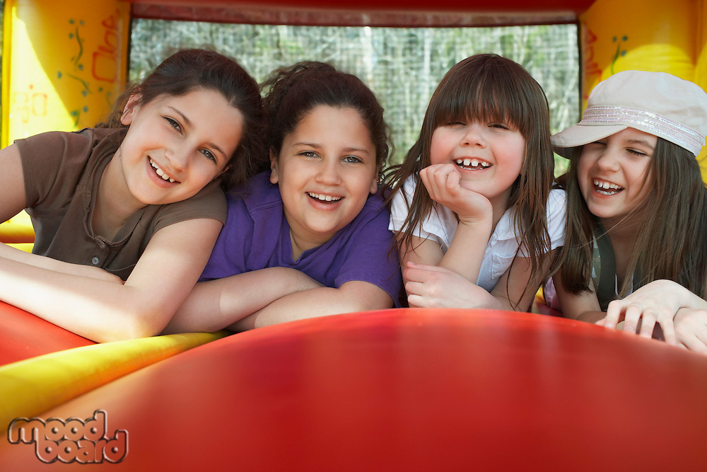Four girls (7-12) lying in row in bouncy castle laughing portrait