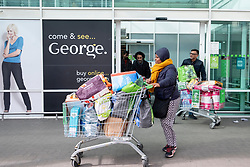 © Licensed to London News Pictures. 15/03/2020. London, UK. Shoppers leave a London Asda supermarket after panic buying items as the Coronavirus disease outbreak spreads across the UK. Household and food items such as pasta, toilet paper and cleaning products have been in short supply. Photo credit: London News Pictures