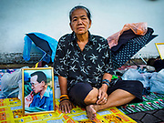 24 OCTOBER 2017 - BANGKOK, THAILAND: A woman with a portrait of Bhumibol Adulyadej, the Late King of Thailand, sits on the side of Atsadang Rd while she waits to enter the royal cremation site. People started camping out along Atsadang Road in Bangkok near the royal cremation site on Monday. The gates won't open until Wednesday morning and the cremation isn't until Thursday night, so most people will sleep outside, on sidewalks and footpaths for three nights. Hundreds of thousands of people are expected to try to get into Sanam Luang, the site of the cremation of Bhumibol Adulyadej, the Late King of Thailand, but the site will only hold about 60,000 people. The Thai government has built replica crematoriums around Bangkok to accommodate the overflow crowds.        PHOTO BY JACK KURTZ