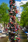 Lovers' padlocks left as romantic love token tradition on bridge at Groenburgwal in Old Town Amsterdam, Holland