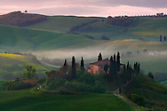 A moody sunrise on a foggy morning at the Belvedere, probably the sweetest spot of the whole Orcia Valley in Tuscany, Italy, from where one can enjoy an extraordinary view on the famous rolling hills, the Mount Amiata and the medieval towns of Pienza, Castiglione and San Quirico. Belvedere is a small hamlet of the municipality of Castiglione d'Orcia, and it is ideally placed at the centre of the Orcia Valley. Taken at dawn on a foggy morning at the beginning of May.