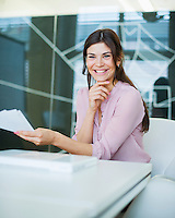 Portrait of smiling young businesswoman with documents at conference table