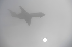 © Licensed to London News Pictures. 01/03/2012. Hounslow, UK. The sun shining through fog as a plane comes in to land at Heathrow Airport on March 1st, 2012. Photo credit : Ben Cawthra/LNP