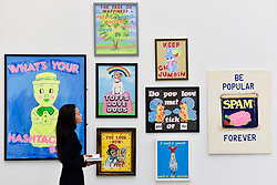 © Licensed to London News Pictures. 12/09/2018. LONDON, UK. A staff member views works advertising inspired works at the preview of START, a contemporary art fair comprising eclectic works from a variety of international emerging artists.  The fair takes place at the Saatchi Gallery in Chelsea 13 to 16 September 2018.  Photo credit: Stephen Chung/LNP