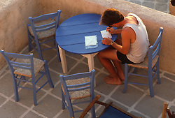 Man at a table in Greece writing postcards and letters