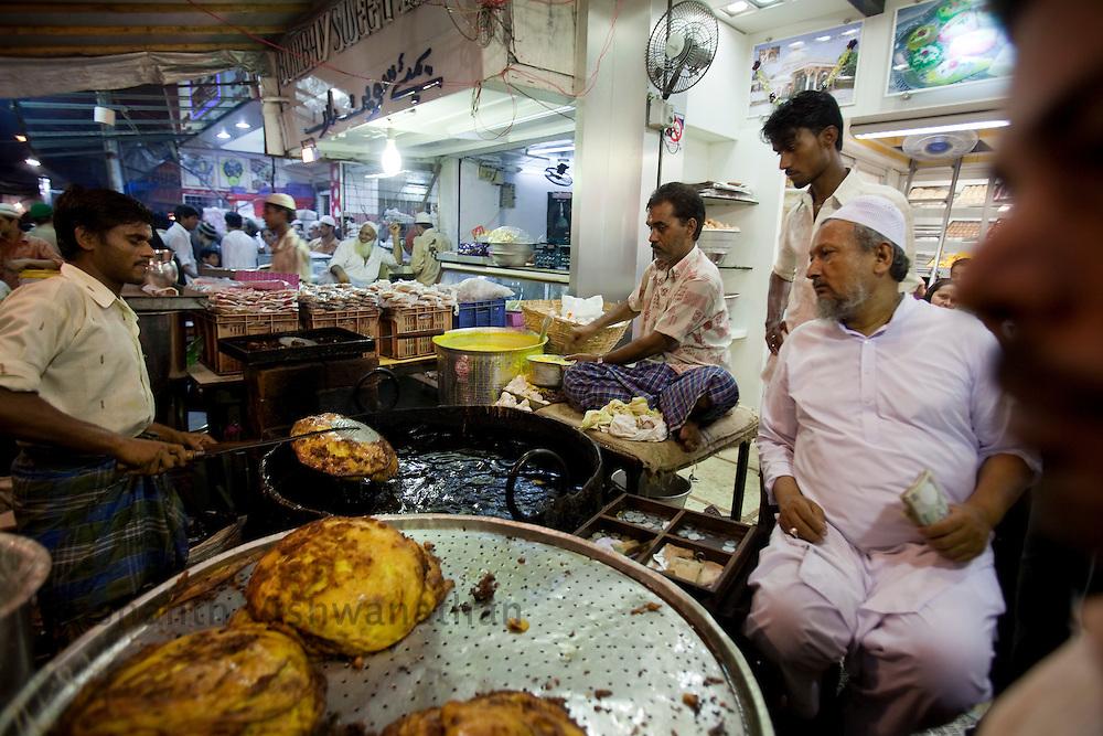 "Abdul Rehman Nasir Khan (R) overlooks as ""Malpua"" a sweet pancake dish is made at a stall, opposite Minara masjid at Mohammed Ali road in Mumbai, Maharashtra, India, on Saturday September 6, 2009. Photographer: Prashanth Vishwanathan/The National"