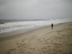 A lone Caucasian man walks along a deserted beach on a cold cloudy day, Quang Binh Province, Vietnam, Southeast Asia.