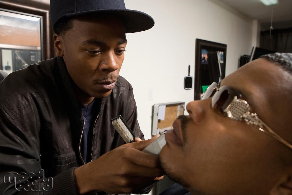 Young man shaving a customers facial hair