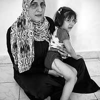 Egypt / Syrian refugees / Syrian refugee Faiza El Ahmed, 33-years-old, holds her daughter Gouda El Ezzi, 3-years-old, in their rented apartment in Beit Al Alia neighborhood in the 6th of October City outside of Cairo, Egypt, Monday, May 27, 2013. Faiza and her daughter have been in Egypt for 2 months and are originally from the Khaledia district in Homs. Gouda broke her leg and required 20 stitches  when government forces attacked their district. Faiza was running with Gouda outside of their house when Gouda slipped and fell and an armored vehicle drove over her leg. It was difficult for them to get to a hospital but when they did one week later doctors put a plate inside of Gouda's leg. / UNHCR / Shawn Baldwin / May 2013