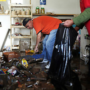 Martin Beruete, left and Efrain Mora clean up the debris inside the Surtidora Mexicana grocery store in the aftermath of massive flooding from Marumsco Creek in Woodbridge.  The flood devastated the Holly Acres mobile home park, but business along Route 1 next to the creek were flooded as well. For The News & Messenger (Manassas, VA)